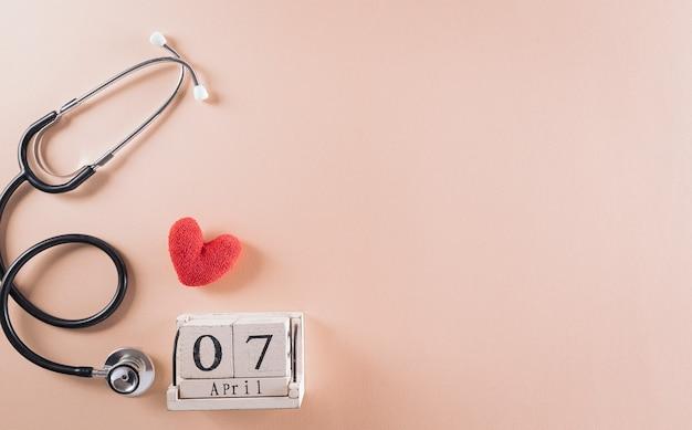 Stéthoscope avec calendrier en bois et coeur rouge sur fond pastel