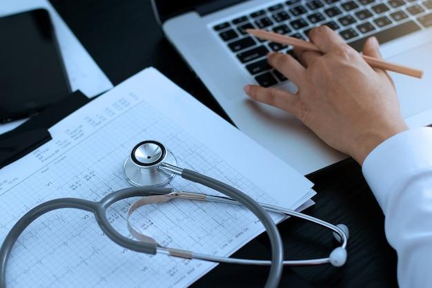 Stéthoscope avec cardiogramme et médecin à l'aide d'un ordinateur portable