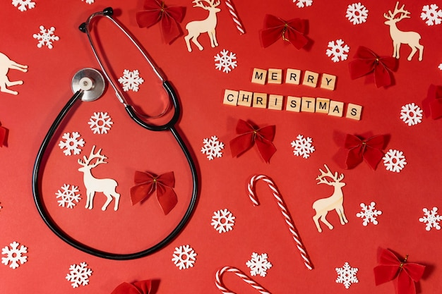 Stéthoscope avec des chapeaux de père noël sur fond rouge avec une inscription de félicitations joyeux noël. concept de clinique médicale de noël