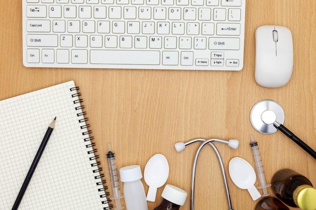 Stéthoscope avec clavier, souris, cahier, crayon, papier blanc et drogue sur fond en bois.