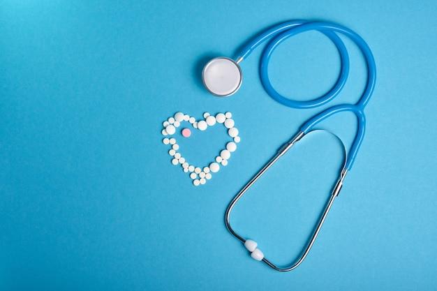 Stéthoscope et coeur de pilules sur une surface bleue