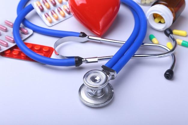 Stéthoscope et coeur rouge, pilules colorées, comprimés, blisters pour la pharmacie et la médecine.