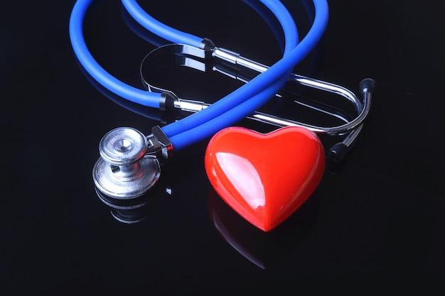 Stéthoscope, cœur rouge et tensiomètre sur fond de miroir noir.