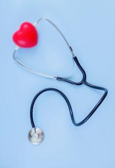 Stéthoscope et coeur rouge sur la vue de dessus de fond de couleur bleue