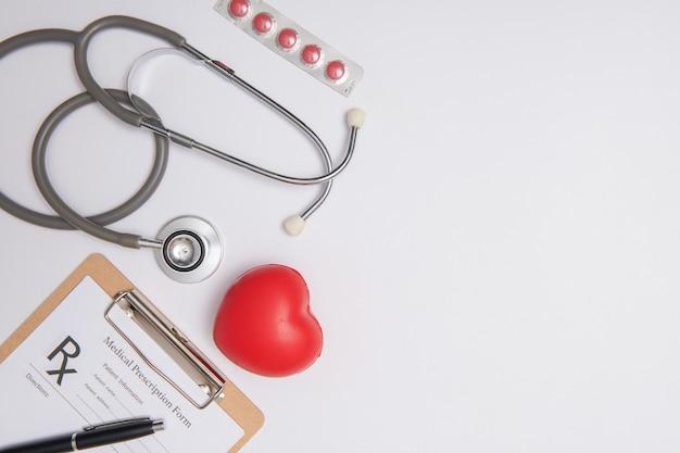 Stéthoscope avec coeur. stéthoscope et coeur rouge sur table en bois. concept d'assurance-vie hospitalière. idée de la journée mondiale de la santé cardiaque. concept de médecine ou de pharmacie. formulaire médical vide prêt à être utilisé.