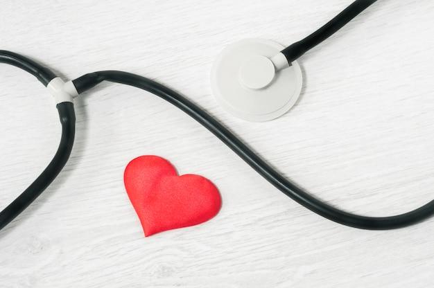 Stéthoscope et coeur sur une vue de dessus de fond clair. concept de soins de santé