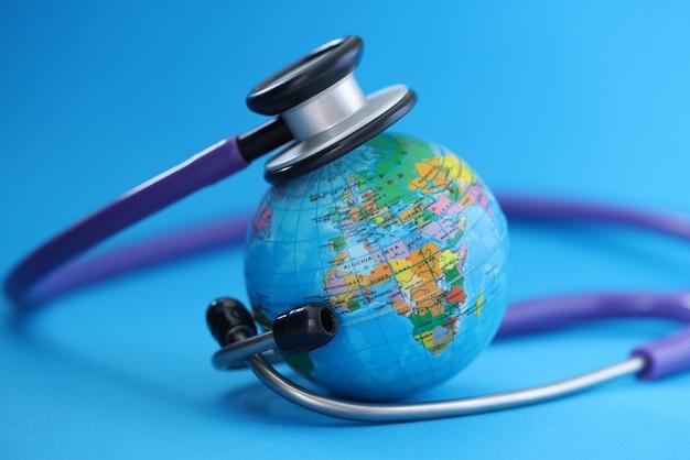 Stéthoscope couché autour du globe sur fond bleu. concept de pandémie de covid-19