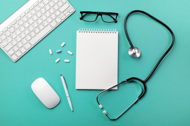 Stéthoscope dans le bureau du médecin avec carnet, stylo, clavier, souris et pilules