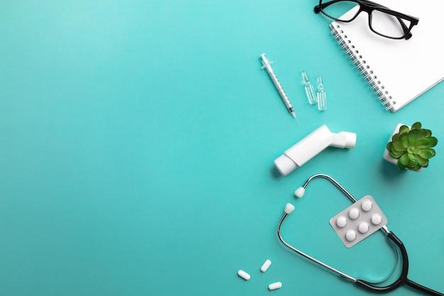 Stéthoscope dans le bureau du médecin avec clavier, seringue, ampoules, inhalateur et pilules