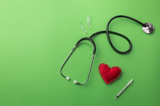 Stéthoscope dans le bureau du médecin avec coeur, seringue et ampoules