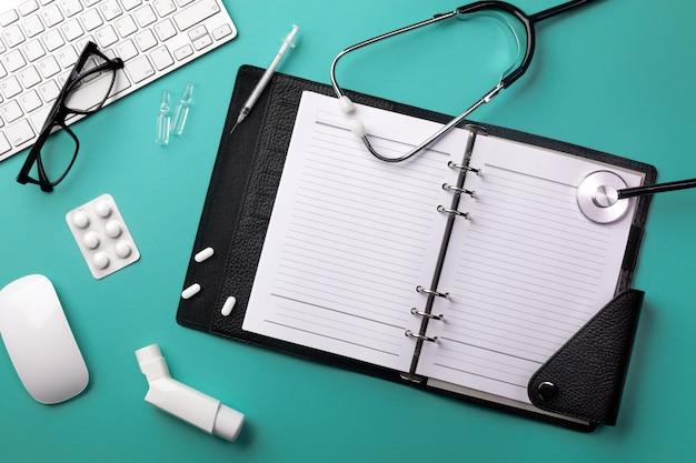 Stéthoscope dans le bureau du médecin avec ordinateur portable, clavier, souris, lunettes, seringue, ampoules, inhalateur et pilules