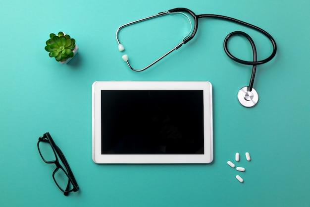 Stéthoscope dans le bureau du médecin avec tablette, lunettes et pilules
