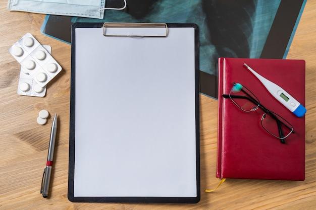 Stéthoscope dans le bureau des médecins. vue de dessus de la table du bureau du médecin, papier vierge sur presse-papiers avec stylo. copiez l'espace. blanc du concepteur