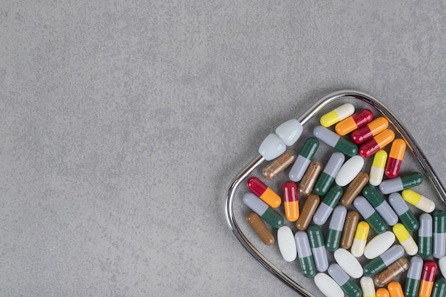 Stéthoscope avec diverses pilules colorées sur une surface grise