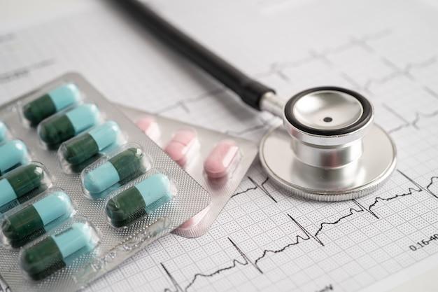 Stéthoscope sur électrocardiogramme avec capsule pilule, onde cardiaque, crise cardiaque, rapport de cardiogramme.