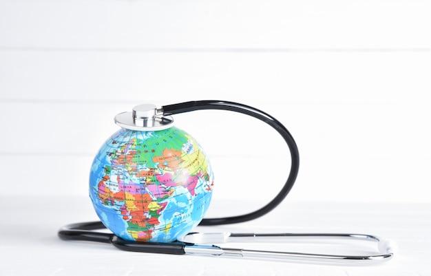 Stéthoscope enroulé autour d'un globe terrestre sur un fond en bois blanc.