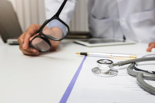 Le stéthoscope est allongé sur le presse-papiers devant un médecin.