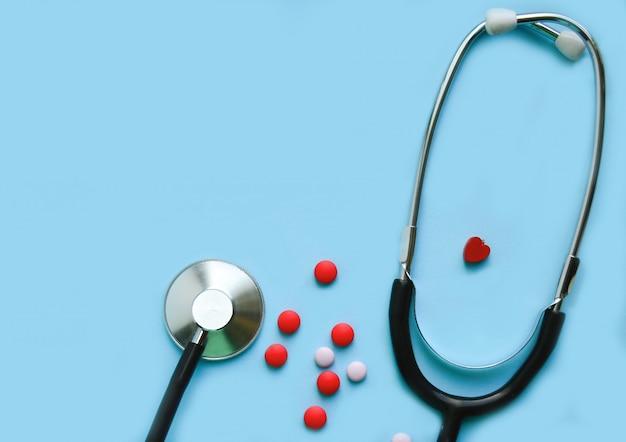 Stéthoscope sur fond bleu avec des pilules et un coeur rouge