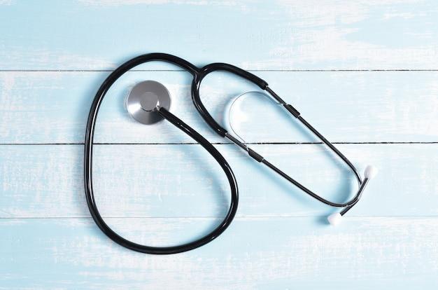 Stéthoscope sur fond en bois pastel blanc. soins de santé mondiaux et concept de la journée mondiale de la santé.