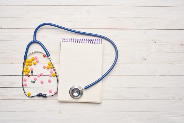 Stéthoscope sur fond de bois pilules vitamines produits pharmaceutiques