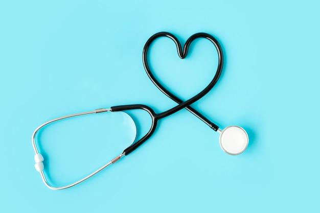 Stéthoscope formant un coeur sur fond bleu pastel.