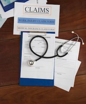 Le stéthoscope et le formulaire de réclamation d'assurance mis sur une planche de bois, une lumière floue autour