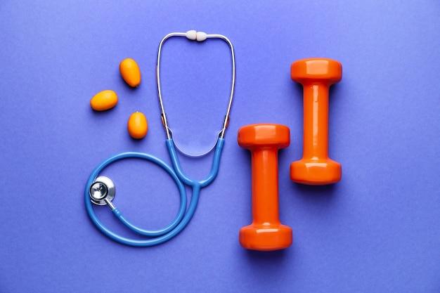 Stéthoscope, fruits et haltères sur la couleur