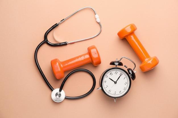 Stéthoscope, horloge et haltères sur fond de couleur