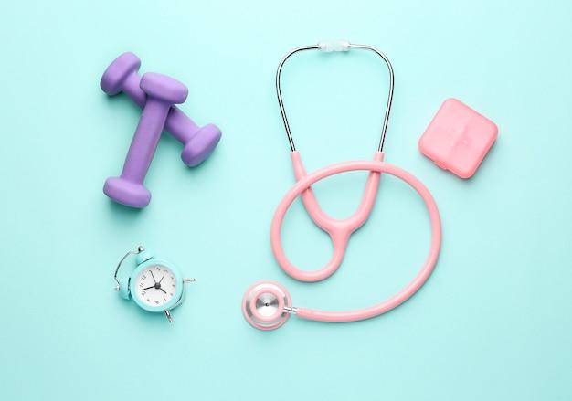 Stéthoscope, horloge, pilules et haltères sur la couleur