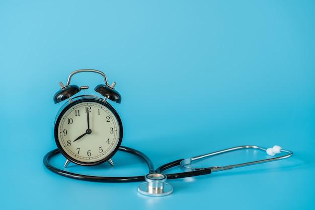 Stéthoscope et horloge vintage sur espace bleu. concept médical et de soins de santé