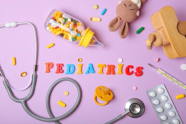 Stéthoscope et jouet de concept de pédiatrie sur un fond clair