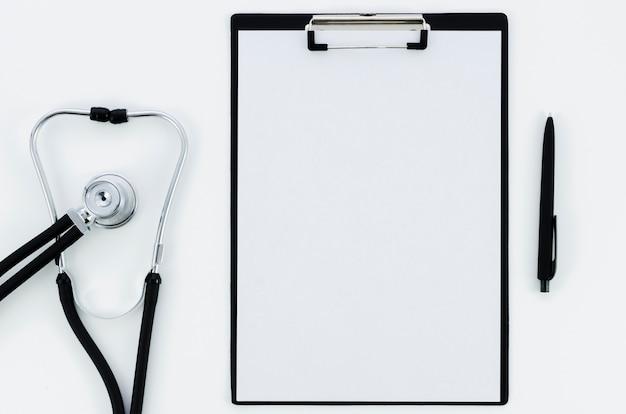 Stéthoscope; livre blanc sur le presse-papiers avec stylo isolé sur fond blanc