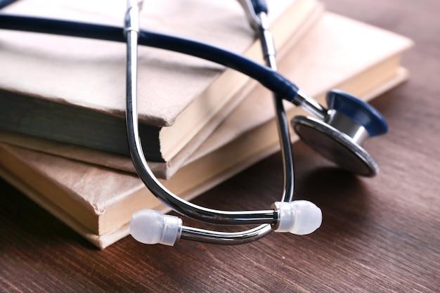 Stéthoscope sur des livres sur table en bois, gros plan