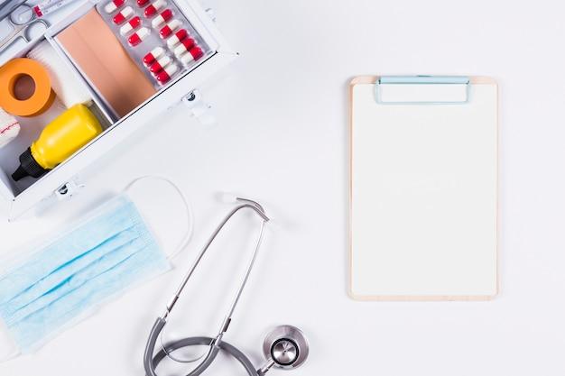 Stéthoscope; masque chirurgical et presse-papiers avec trousse de premiers soins sur fond blanc