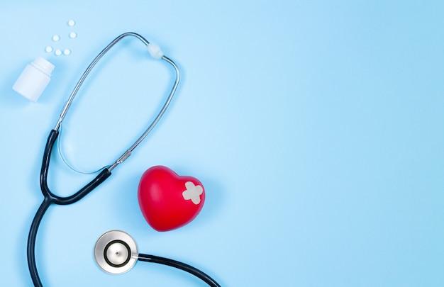 Stéthoscope de médecine, bouteille de pilules et coeur rouge avec vue de dessus en plâtre sur table de cardiologue