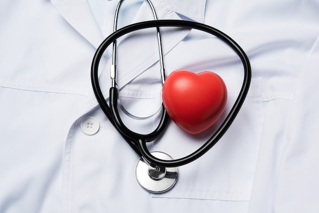 Stéthoscope médical et coeur en caoutchouc rouge sur une surface blanche, vue du dessus