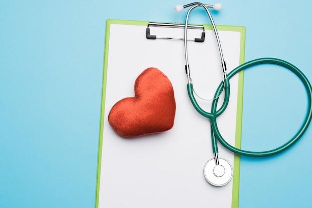 Stéthoscope médical et coeur textile rouge sur fond bleu, vue du dessus