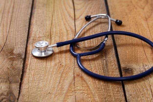 Stéthoscope médical et comprimés isolés sur bois