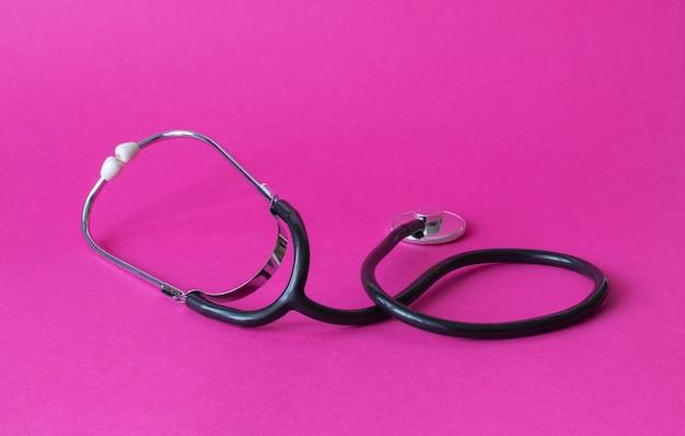 Stéthoscope médical sur fond rose. antécédents en soins de cardiologie et cardiologie