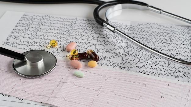 Stéthoscope médical avec pilules et cardiogramme sur fond clair