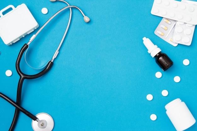 Stéthoscope médical avec des pilules sur fond bleu.