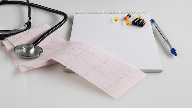 Stéthoscope médical avec pilules et tonomètre sur surface blanche. prescription médicale