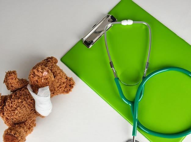 Stéthoscope médical et porte-papier vert sur un blanc, à côté d'un ours en peluche