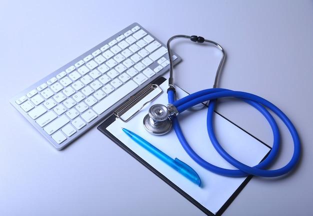 Un stéthoscope médical près d'un ordinateur portable sur une table en bois