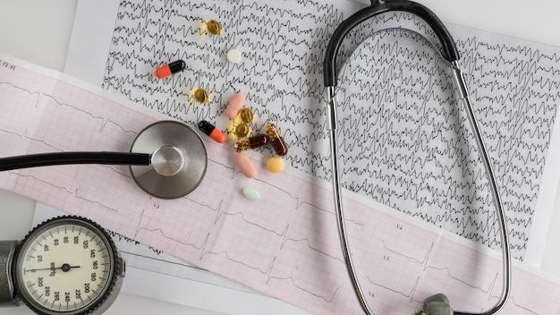 Stéthoscope médical avec tonomètre et ecg sur fond clair. vue de dessus