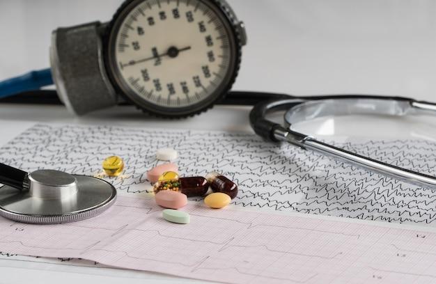 Stéthoscope médical avec tonomètre et ecg sur fond clair