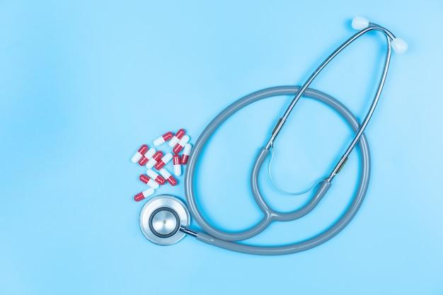 Stéthoscope avec médicament en capsule sur fond bleu