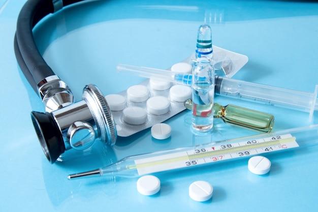 Stéthoscope et médicaments avec thermomètre sur fond bleu.