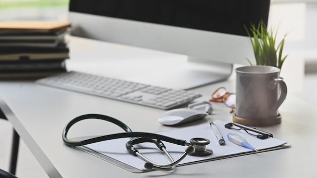 Stéthoscope mettant sur un bureau de travail blanc avec tasse de café, plante en pot, presse-papiers, souris et clavier sans fil, pile de livres, espace de travail du médecin dans le centre médical.