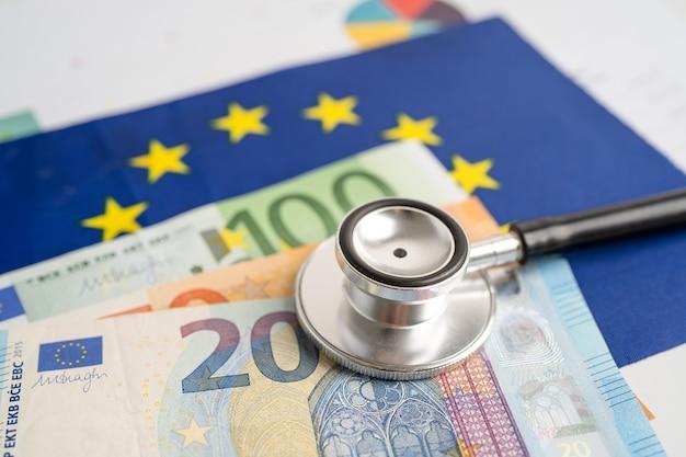 Stéthoscope noir sur le drapeau de l'ue en europe avec des billets de banque, concept commercial et financier.